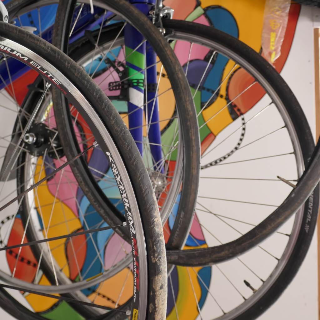 Bike wheels with colourful wall in the background.